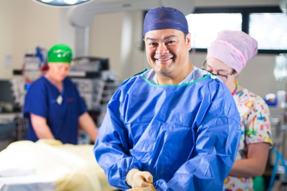 image of Associate Professor Kelvin Kong smiling at the camera in scrubs in operating theatre with two health professionals in the background