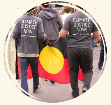 back of two people in black pants & t-shirts with words 'Climate Justice Now!' holding Aboriginal flag