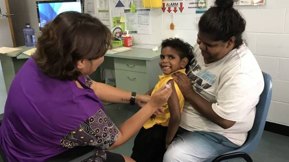 Aboriginal mum sitting holding standing young child getting a vaccine by health worker
