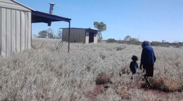 photo of elderly woman and small child walking through dry grasses to tin shed
