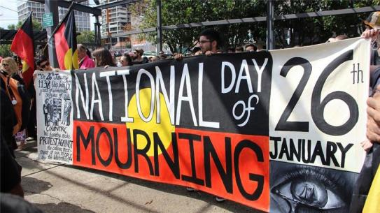 Aboriginal people with large banner National Day of Mourning 26 January