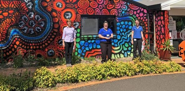 CSU lecturer in physiotherapy & placement supervisor Kay Skinner with CSU physiotherapy students Emily Barr and Kloe Mannering standing outside an ACCHO with brick walls covered in Aboriginal paintings