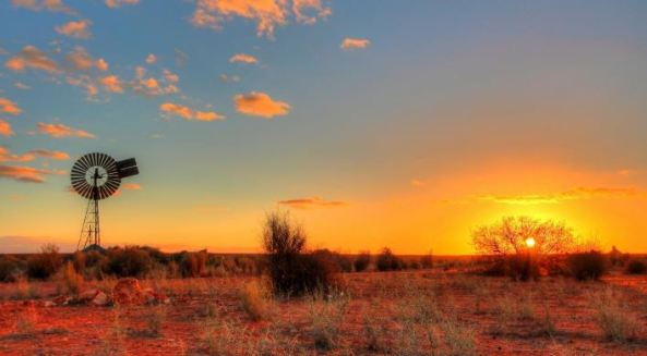 dry SA landscape with sun setting, windmill & sparse vegetation, red dirt