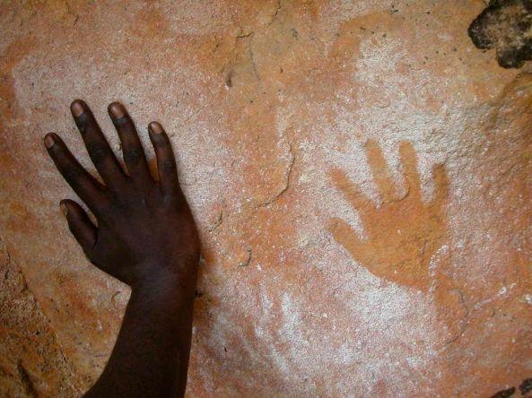 Gundjeihmi Aboriginal rock art hand stencil and Aboriginal hand against the rockhand