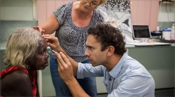 Dr Rallah-Baker checking elderly Aboriginal woman's eyes with torch