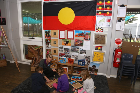 three girls with teacher on mat in Goodstart Early Learning Bathurst, Aboriginal flags & images in background
