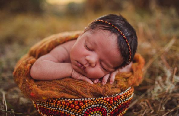 sleeping Aboriginal baby in orche coloured blanket in bowl with Aboriginal dot painting & Aboriginal colour headband all sitting in dry grass landscape
