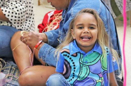 young Aboriginal girl with huge smile looking to the camera, wearing blue aqua purple Aboriginal dot painting polo, two Aboriginal women in the background making baskets from raffia
