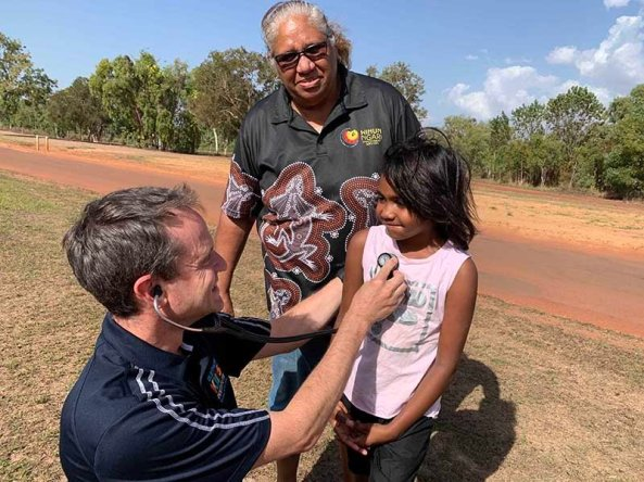 doctor in field listening to Aboriginal girl's heart, overseen by AHW