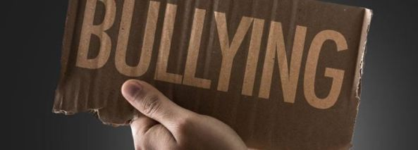 hand holding piece of ripped carboard with text 'BULLYING' in capitals