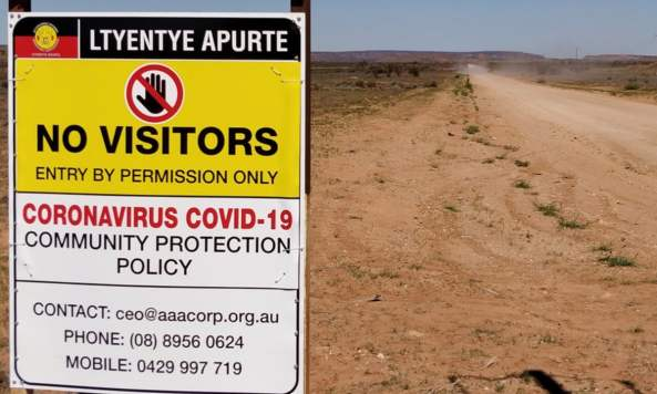 Ltyentye Apurte No Visitors COVID-19 Community Protection Policy sign on outback dusty road