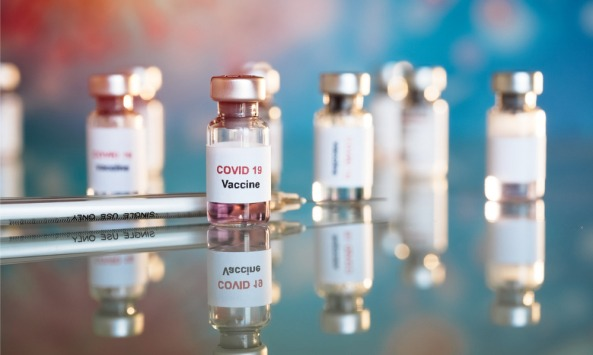 9 vials of COVID-19 vaccine with syringe on a mirrored surface