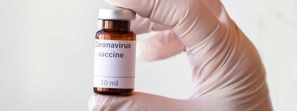 gloved hand holding vial with words Coronavirus vaccine 10 ml