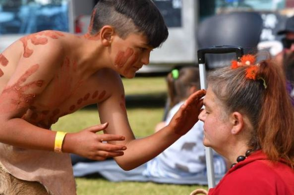 Cruze Smart-Pitchford, 12, with Aboriginal body paint & skin skirt painting mother Karen Smart-Pitchford with ochre before a welcome to country ceremony at Noi.heen.ner