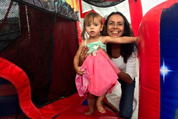 Tanya Day with small girl on indoor play equipment