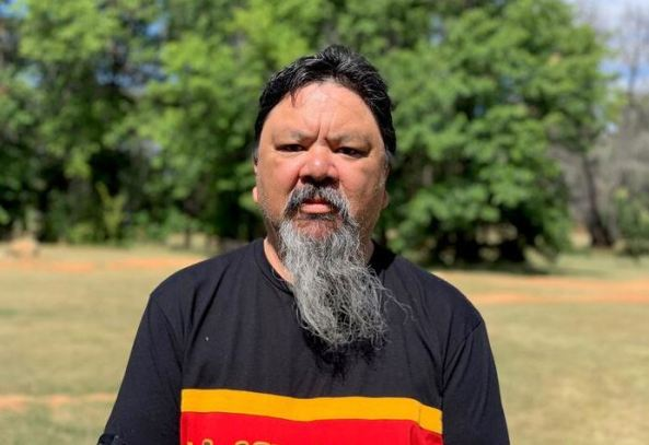 Diabetes Australia's Indigenous engagement manager Christopher Lee standing on an oval with large green trees in the background, wearing black yellow and red t-shirt
