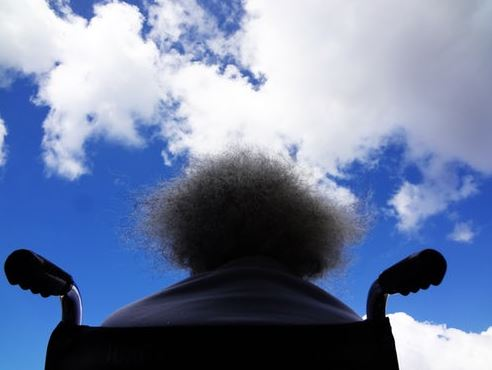 rear view of older Aboriginal woman in wheelchair looking at white clouds against a blue sky