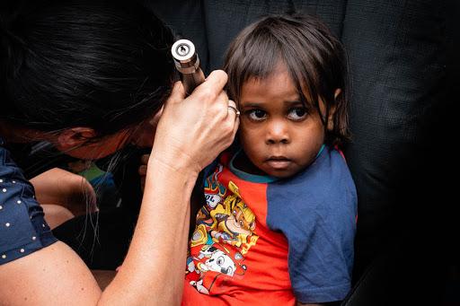 health professional checking a small Aboriginal child's ear