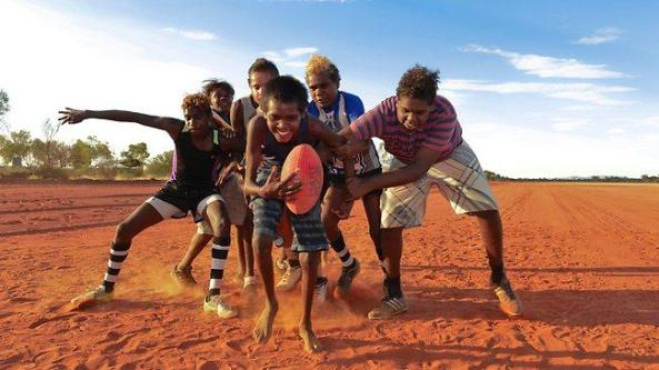 group of Aboriginal boys on red dust landscape - Yuendumu footballer Messiah Brown (centre) is sheperded by Jerome Dickson as Ezekial Egan (stripy shirt) and Riley White try to tackle him