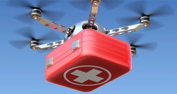 red box with white cross in a circle attached to drone, against blue sky