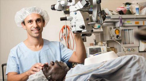 Dr Kris Rallah-Baker (Yuggera & Biri-Gubba-Juru/Yuggera man, first Indigenous ophthalmologist). (Fred Hollows Foundation) in scrubs, holding eye medical machine over Aboriginal man lying on hospital bed