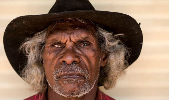 close up image of face of elderly Aboriginal stockman with felt hat, blind in one eye