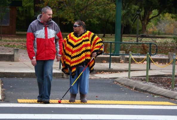 Aboriginal woman with poncho in Aboriginal flag colours, walking cane on road with man assisting