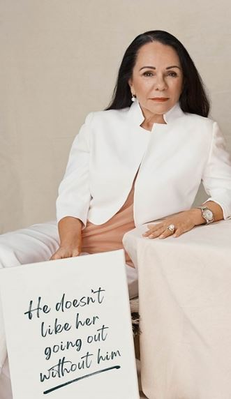 photo of LInda Burney MP, Shadow Minister for Indigenous Australians holding sign 'He doesn't like her going out without him'P