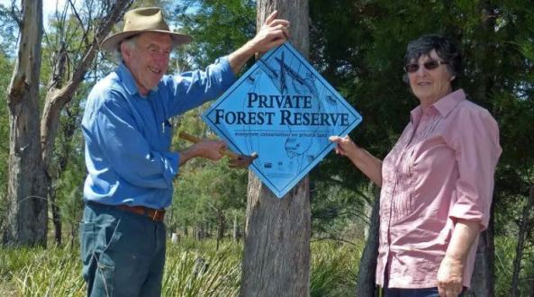 Tom and Jane Teniswood holding 'Private Forest Reserve' sign on a tree trunk