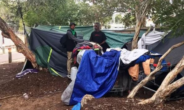 Two homeless Aboriginal men in front of a makeshift tent in Perth