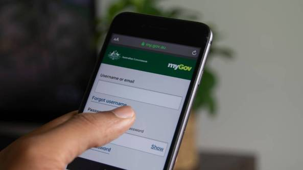 thumb clicking mobile phone screen with myGov app showing