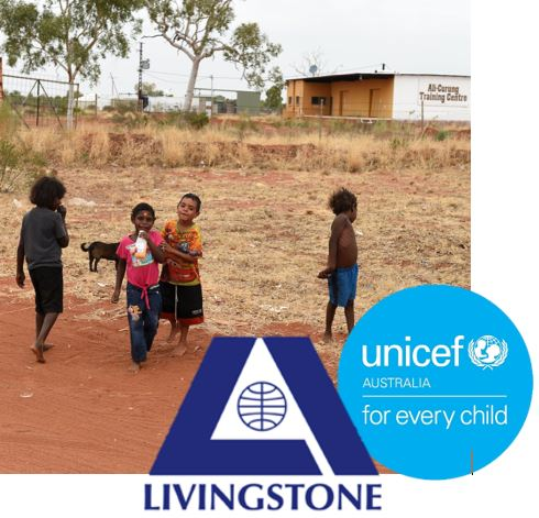 4 young Aboriginal kids red dust with Ali-Curung Training Centre NT uilding in the background, overlaid with UNICEF Australia & Livingstone International logos