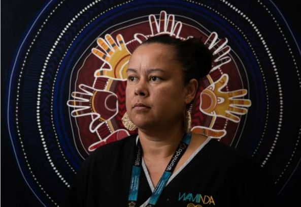 portrait of Mel Briggs, Waminda midwife against Aboriginal painting of silhouette of hands in a circle surrounded by Aboriginal circles in dots