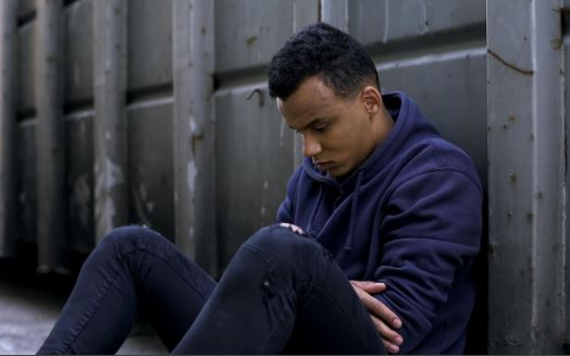 young Aboriginal man sitting against wall with head down, arms folded, blue hoodie & jeans