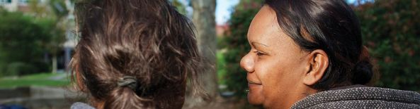 rear view of heads of two Aboriginal women, one looking sideways at the other, set against blurred background of green street foliage