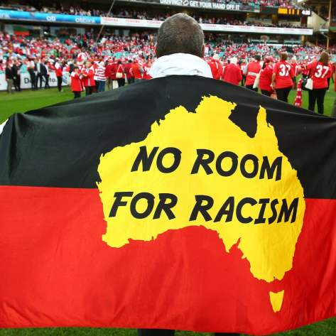 back of man at football with flag in Aboriginal colours, yellow centre with map of Australia & text ' no room for racism'