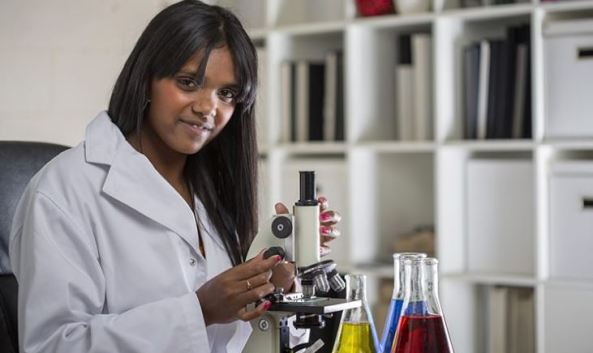Aboriginal woman in lab coat with microscope and beakers with yellow blue & red liquidr