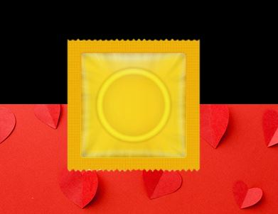 red cardboard with cut out raised hearts bottom half rectangle, black top half of rectangle & image of yellow condom packet in the middle
