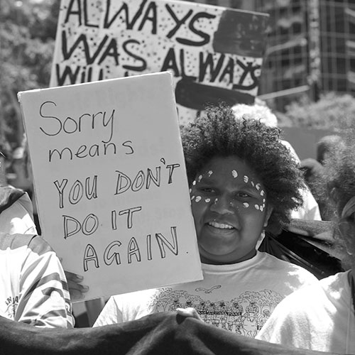 black and white photo of Aboriginal woman with Aboriginal body paint on face standing in crowd with a sign 'Sorry means you don't do it again', placard in background says 'Always was, Always will be'