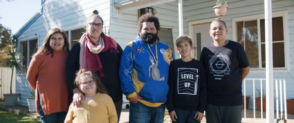 Wiradjuri woman Charlotte Porter & her husband James & their 4 children standing in front of their home