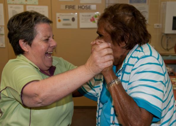 health care professional laughing with elderly Aboriginal woman, standing, hands held raised