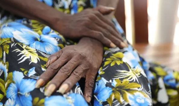 close up image of Aboriginal woman's hands resting on her knees, floral dress