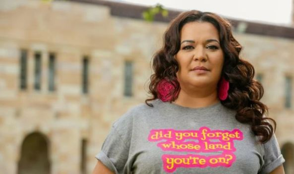 Associate Professor Chelsea Watego standing in front of UQ buildings with grey t-shirt & words 'did you forget whose land you're on?'
